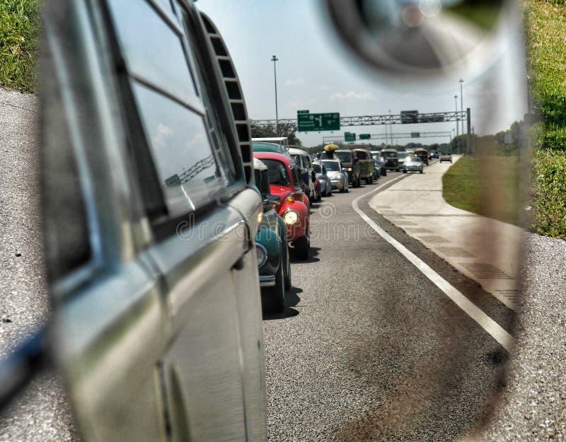 Lång rad av bilar i rearvewspegel arkivfoto