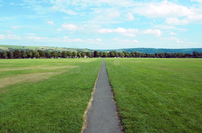 Lång rak vandringsled i en parkera med gräsgräsmatta och landskap arkivbilder