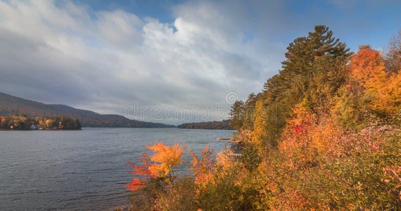 Lång sjö, Adirondacks, NY, i nedgången som omges av briljant färgrik lövverk royaltyfria bilder