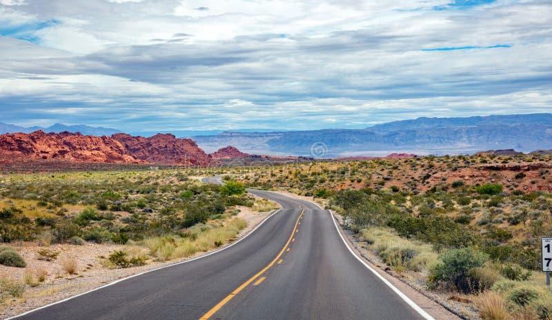 Lång slingrig huvudväg med med- och motgångar, molnig blå himmel Dal av brand Nevada, USA royaltyfria bilder
