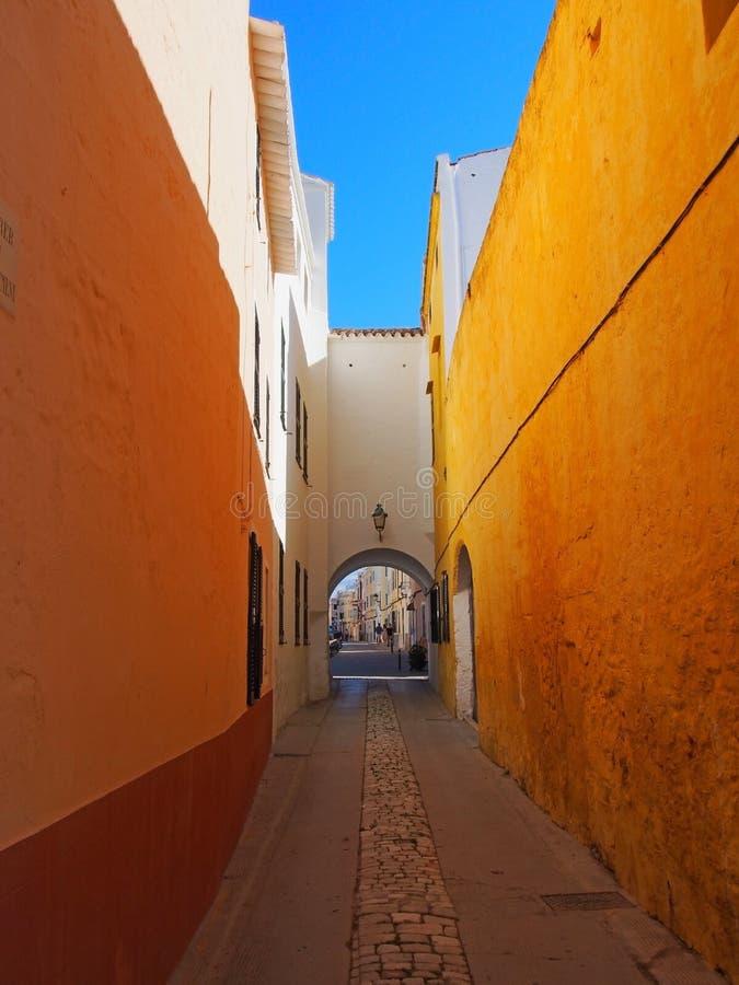 Lång smal gränd i ciutadellastadmenorca med en ljus gul vägg och valvgång på slutet med en blå sommarhimmel royaltyfria foton