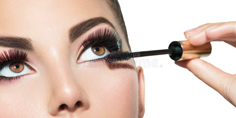 Lång snärtcloseup Härlig kvinna som applicerar mascara på henne ögon royaltyfria foton