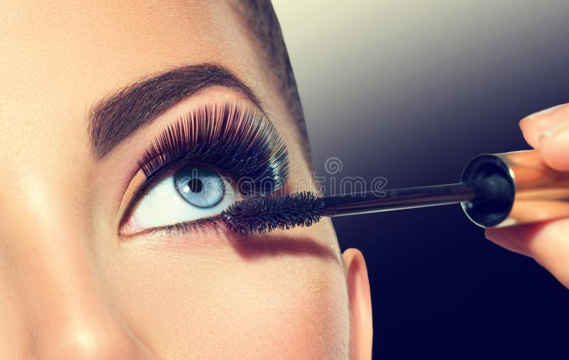 Lång snärtcloseup Härlig kvinna som applicerar mascara på henne ögon royaltyfria bilder