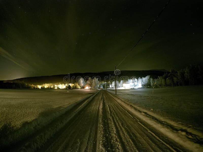 Lång snöig lantgårdväg på midnatt med hus arkivbild