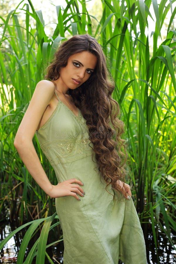 lång ståendekvinna för härligt lockigt hår arkivfoton