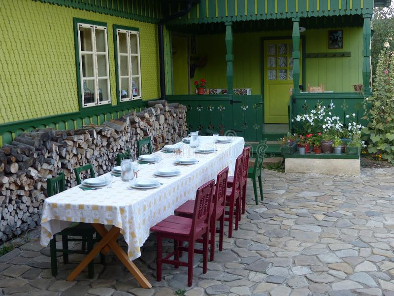 Lång tabell som är förberedd ut ur ett grönt wood hus i Rumänien royaltyfri fotografi