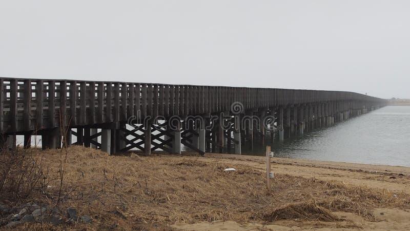 Lång träbro som går in i dimman över vatten i vinter fotografering för bildbyråer