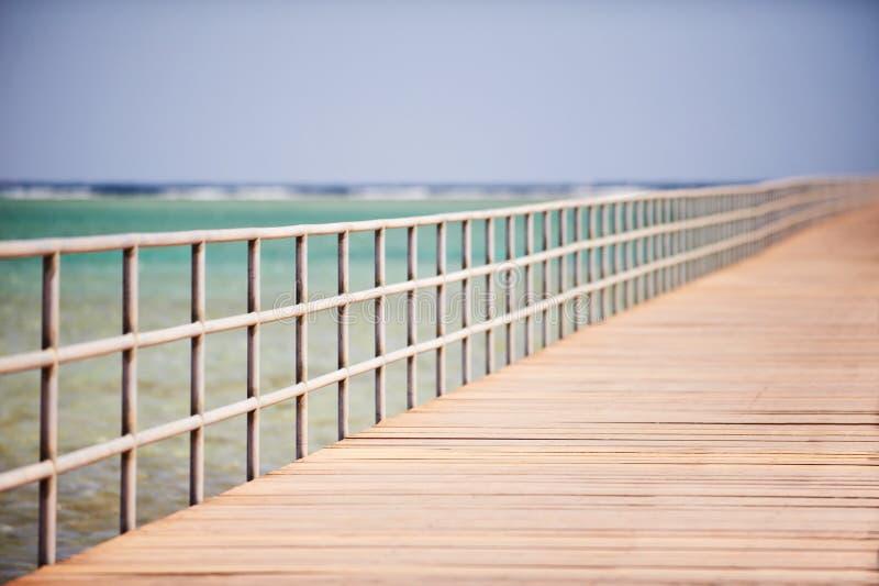 Lång träbrygga på Röda havet royaltyfri foto
