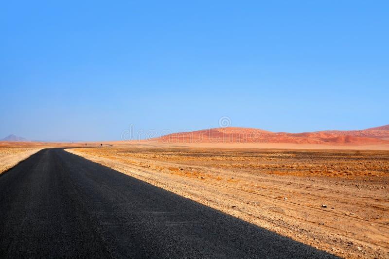 Lång väg för tom svart asfalt, dyn för Namib öken och bakgrund för blå himmel, trans.designmall, ingen, kopieringsutrymme royaltyfri fotografi