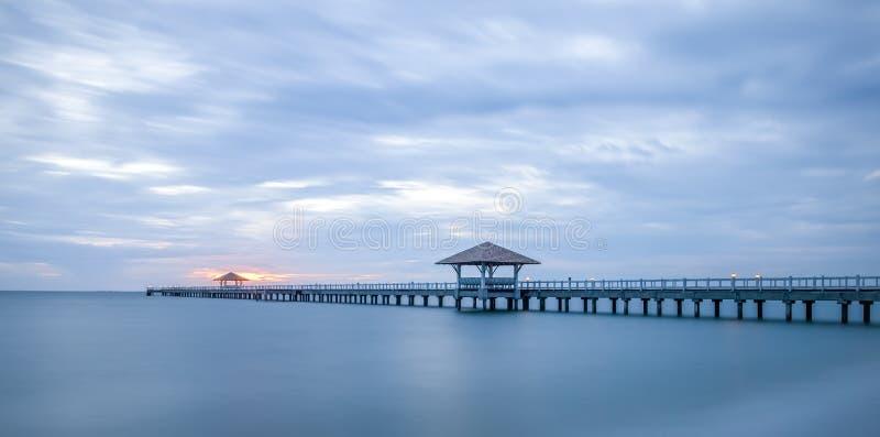 Lång wood bro på havet i solnedgång royaltyfria foton