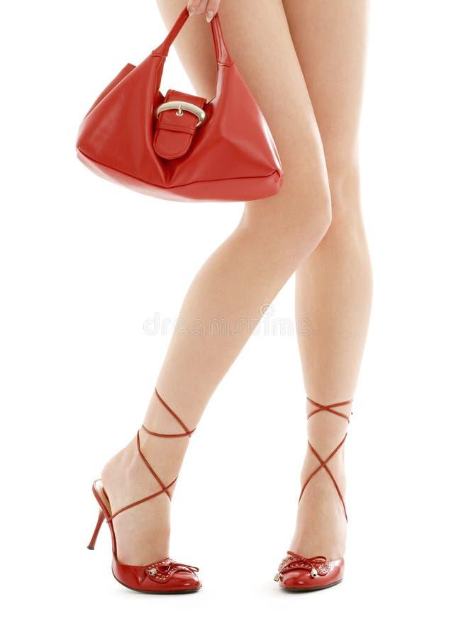 Långa ben på höga häl och den röda handväskan arkivfoto