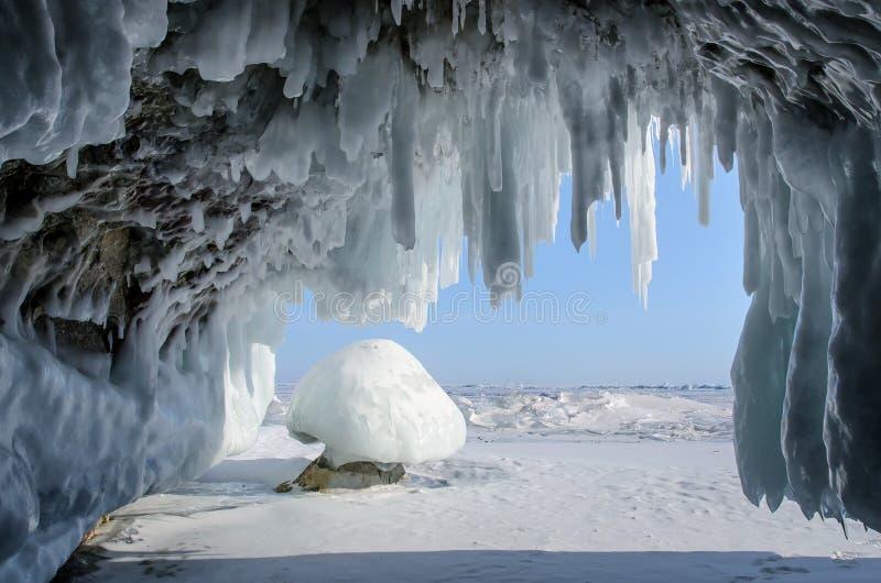 Långa blåa istappar i isgrottan på kust- klippor royaltyfria bilder
