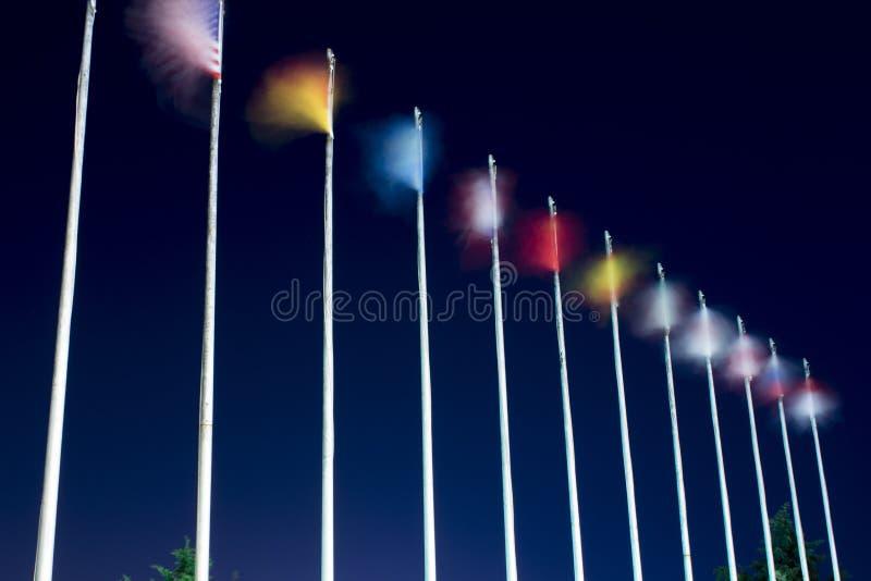 Långa exponeringsflaggor Vinkande flaggor på vinden på natten Olika landsflaggor är på pelarna arkivfoton