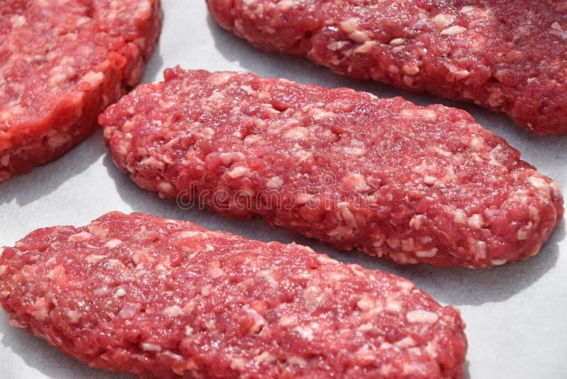 Långa kebaber för rått mörkt kött, kotletter på pergament arkivbilder