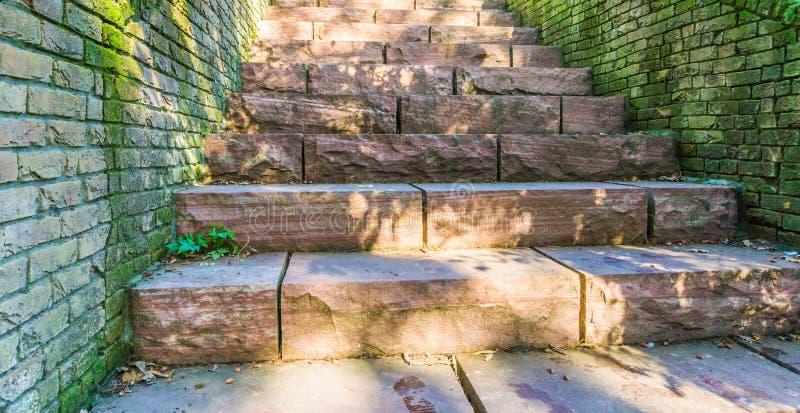 Långa röda stentrappuppgångmoment som göras ut ur den stora granitstenen, blockerar gammal retro stilbakgrundstextur arkivfoton