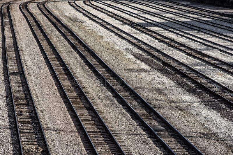 Långa raden av det åtskilliga järnvägdrevet spårar tomt utan drev i trainyard arkivfoto