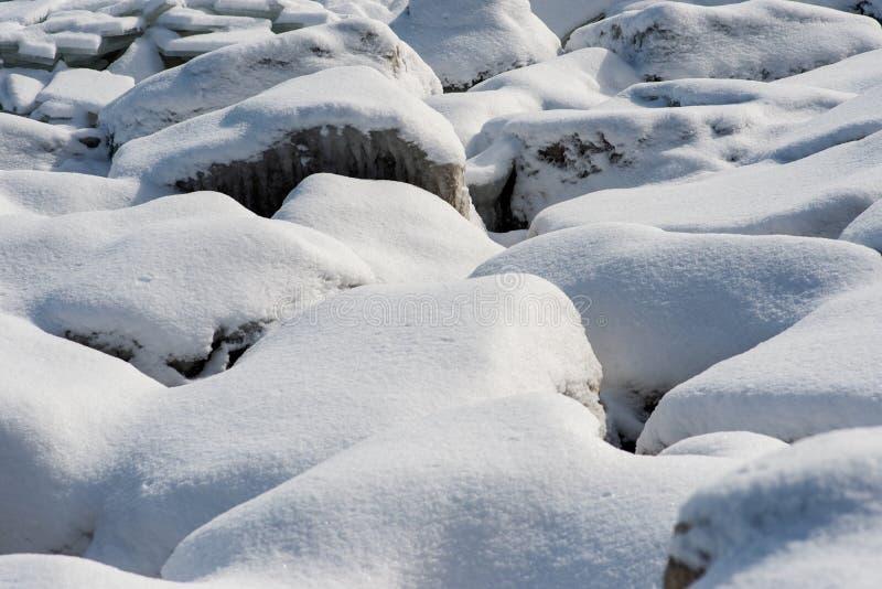 Långa raden av vaggar längs Lake Michigan shoreline som täckas med djupfryst is och snö på en solig vinter royaltyfri bild