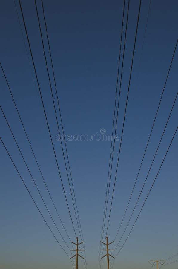 Långa raderna av maktpolerna i den dammiga blåa himlen arkivfoton