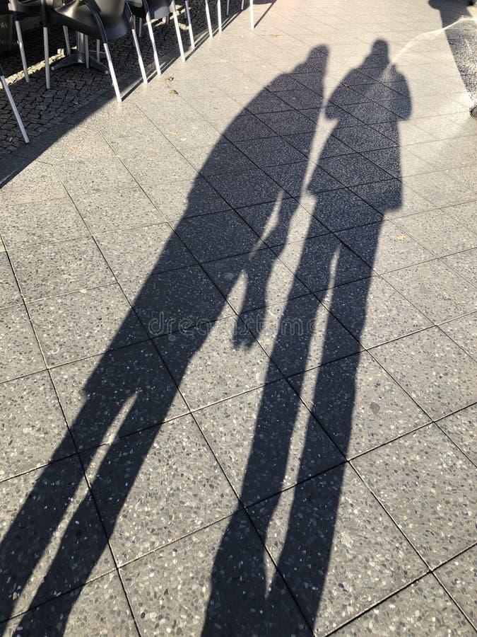 Långa skuggor av två personer på trottoaren arkivfoton