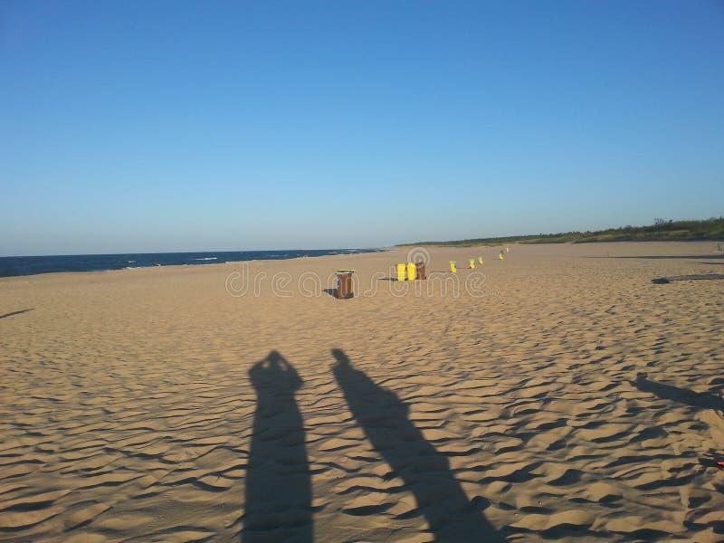 Långa skuggor på stranden royaltyfria bilder