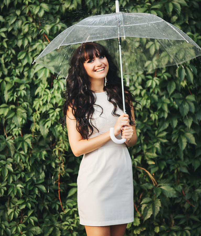 Långhårig brunett i den vita klänningen med paraplyet arkivbilder