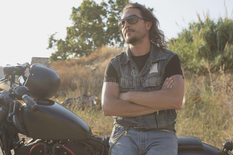 Långhårig brunettgrabb som poserar på en svart beställnings- motorcykel arkivbild