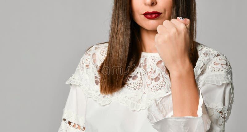 Långhårig dominera näve för brunettkvinnavisning royaltyfria foton