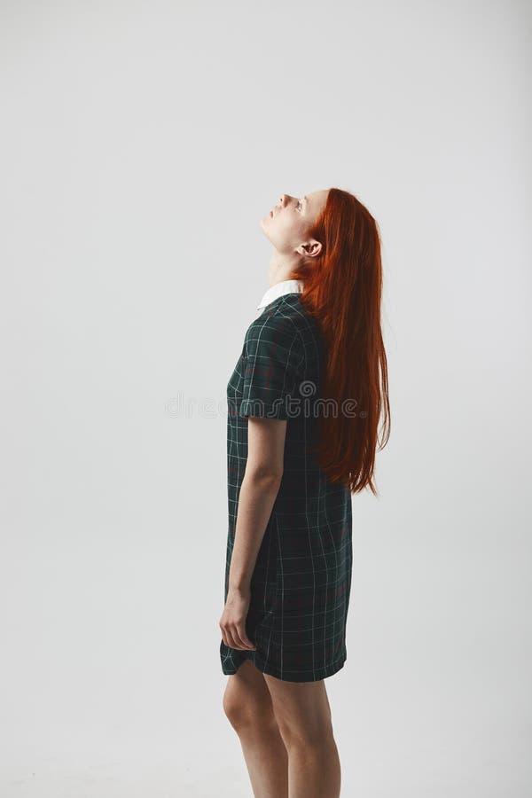 Långhårig flicka för härlig rödhårig man i en grön rutig klänningställning på den vita bakgrunden i studion royaltyfria foton