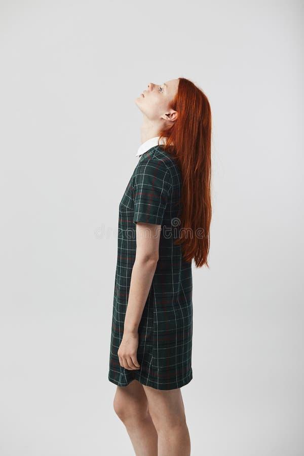 Långhårig flicka för härlig rödhårig man i en grön rutig klänningställning på den vita bakgrunden i studion royaltyfri fotografi