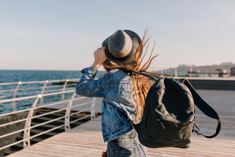 Långhårig flicka i grov bomullstvilldräktblickar in i havet långt, medan vind spelar med hennes mörka hår Stilfull ung kvinna i h royaltyfria foton