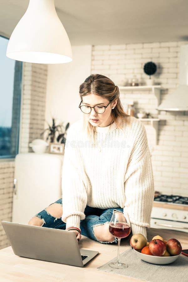 Långhårig flicka i stilfull ojämn jeans som arbetar på hennes bärbar dator royaltyfri fotografi