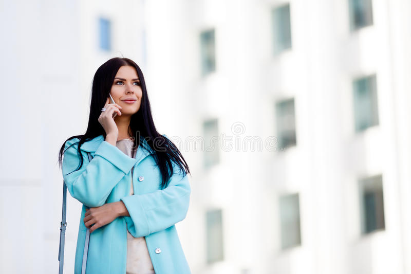 Långhårig flicka med telefonen utomhus royaltyfri foto