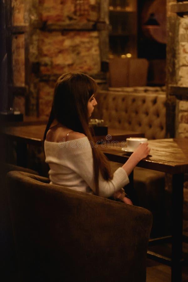 Långhårig härlig flicka i en vit tröja som sitter i en coffee shop på en trätabell som dricker kaffe, en ensam flicka, sikt från royaltyfria bilder