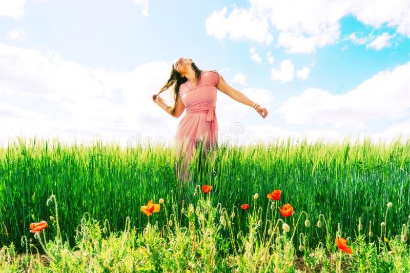 Långhårig kvinna i en rosa klänning på ett fält av grönt vete och lösa vallmo arkivbilder