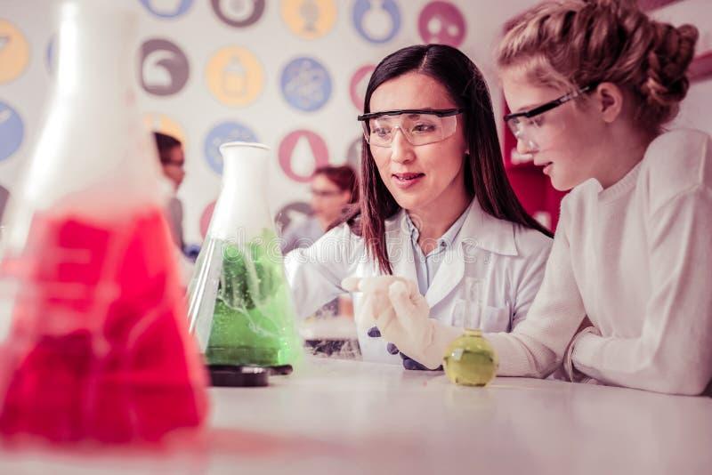 Långhårig kvinna som arbetar i skola och har kemiskt experiment royaltyfri foto