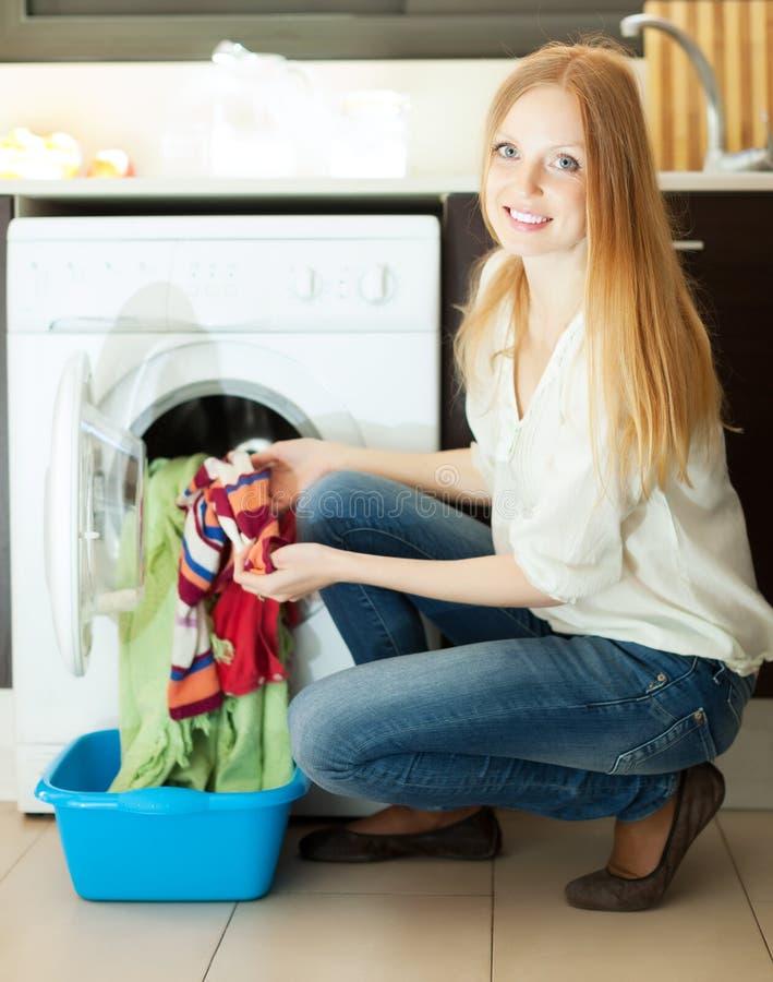 Långhårig kvinna som gör tvätterit arkivfoto