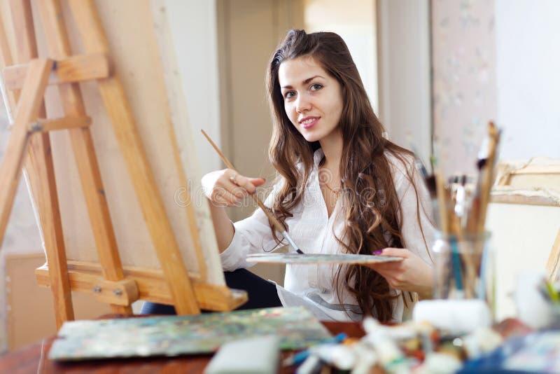 Långhårig kvinnlig konstnärmålarfärgbild på kanfas arkivbild