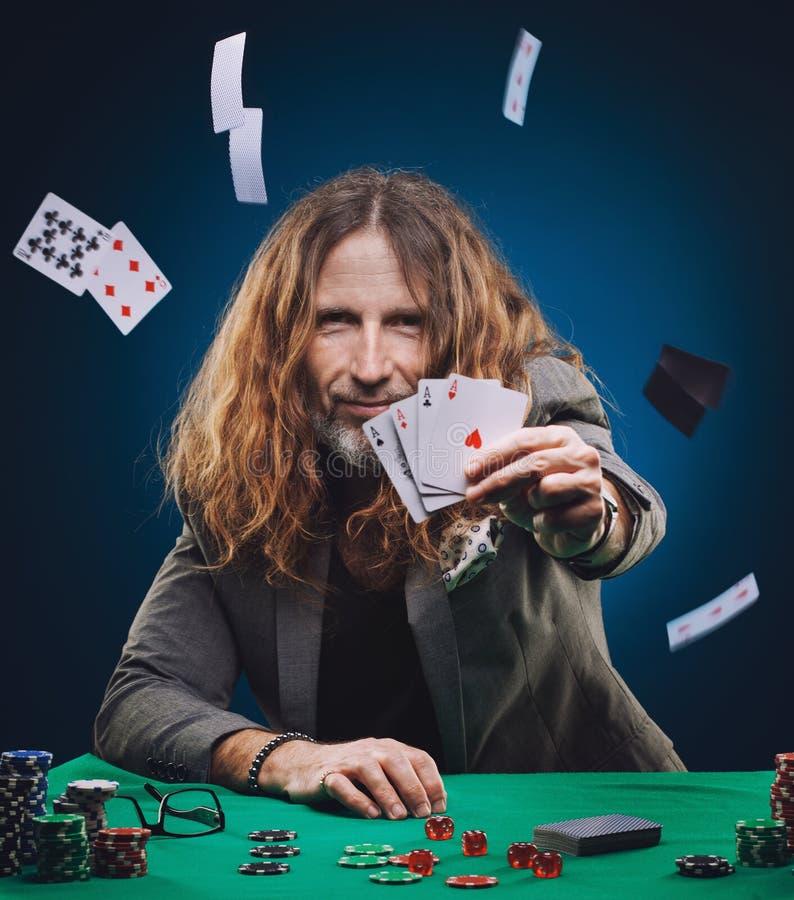 Långhårig stilig man som spelar poker i en kasino royaltyfria foton