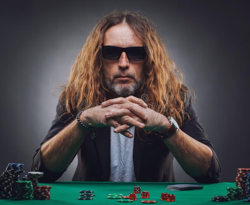 Långhårig stilig man som spelar poker i en kasino royaltyfri bild
