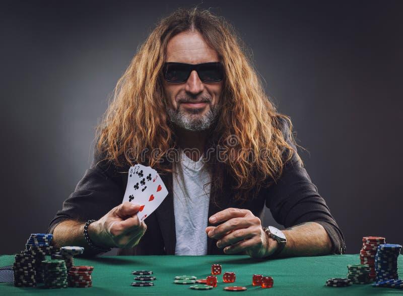 Långhårig stilig man som spelar poker i en kasino royaltyfri fotografi