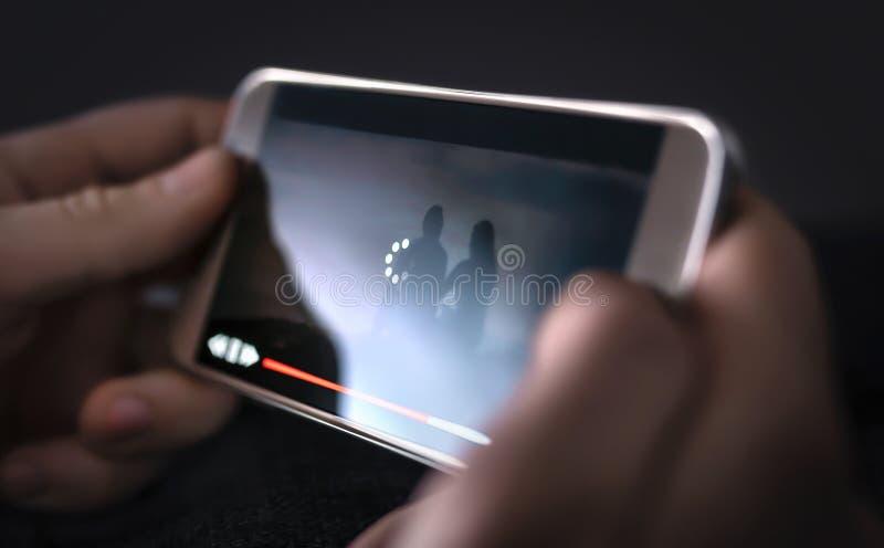 Långsam internet, video påfyllning och nedladdninghastighet Online-h?llande ?gonen p? film Ladda symbolen på skärmen royaltyfri foto