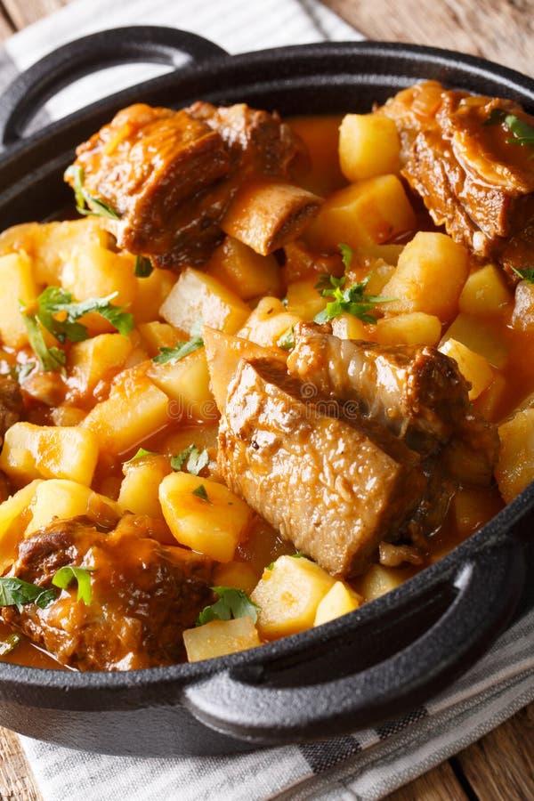 Långsamt kokta korta nötköttstöd med potatisar och skynärbild i en kruka vertikalt arkivbild