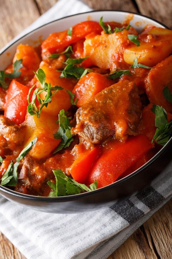 Långsamt lagat mat nötkött med potatisar, tomater, peppar, morötter och på royaltyfri foto