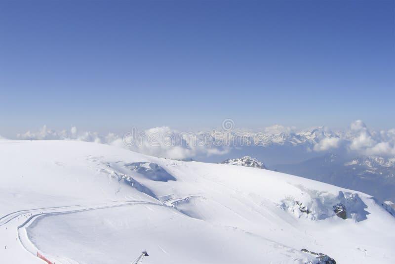 Långt alpint spår n för skida mycket överkanten av schweiziska fjällängar arkivfoto