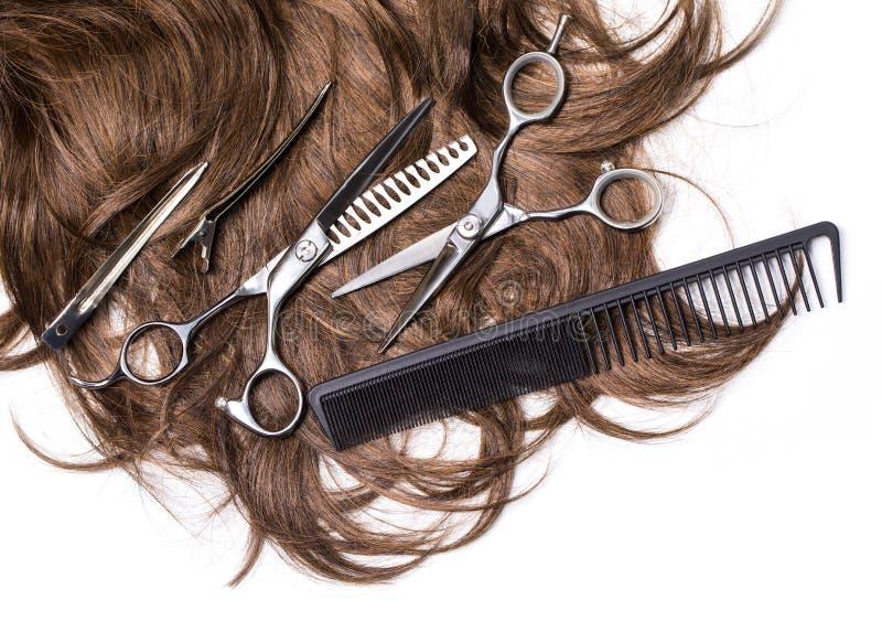 Långt brunt hår med sax royaltyfria bilder