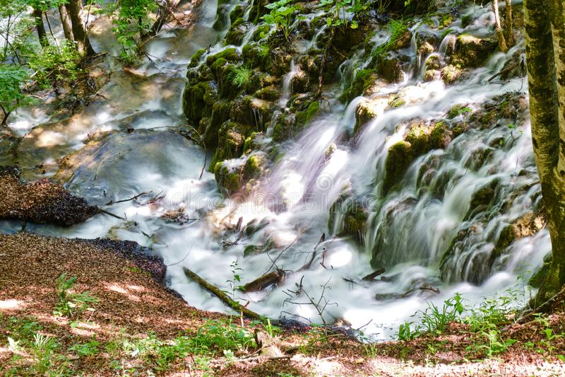 Långt exponeringsfoto av vattenfallet som flödar till och med en skog, på Plitvice sjönationalparken, Kroatien ovanf?r sikt royaltyfri fotografi