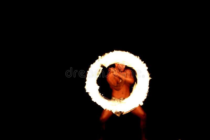 Långt exponeringsskott av en infödd fijiansk branddansare som utför en brandcirkel arkivbilder