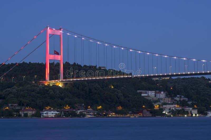 Långt exponeringsskott av Fatih Sultan Mehmet Bridge FSM med ljusa slingor efter solnedgång över bosphorus i Istanbul, Turkiet royaltyfri bild