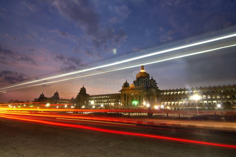 Långt exponeringstrafikskott av Vidhana Soudha delstatsparlamentbyggnaden i Bangalore, Kanataka, Indien arkivfoto