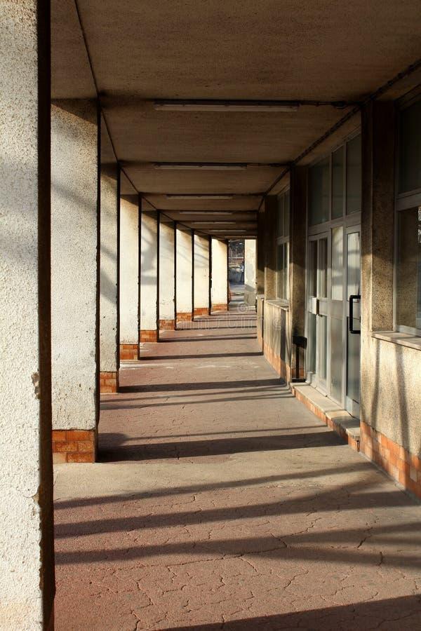 Långt hall för konkreta pelare som stöttar det bästa golvet och stora ingångsdörrar på sidan som monteras på sprucket golv av öve arkivfoton